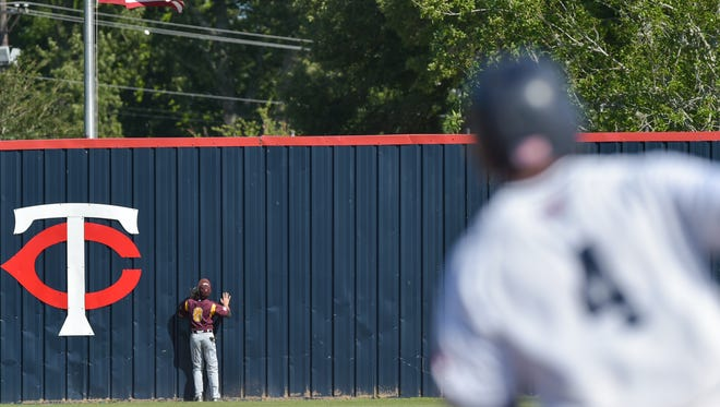 Centerfielder Cody Watkins watches Nick Weber's ball clear the wall as the Teurlings Rebels host the Grant Cougars.