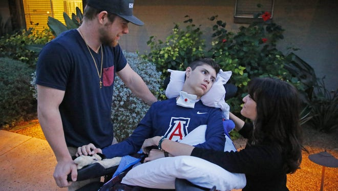Hunter Higgins and Mali Rose visit with Andrew Ochoa at his rehab facility Tuesday, Feb. 21, 2017 in Phoenix, Ariz.