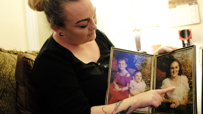 Amber Sawyer of Pascagoula, Miss., holds two framed photos March 16, 2018, with herself when she was 8, left, her sister Angela was 4 and her oldest sister, Donna, was 21. The photo was taken several months before her sister Donna committed suicide in 1988.