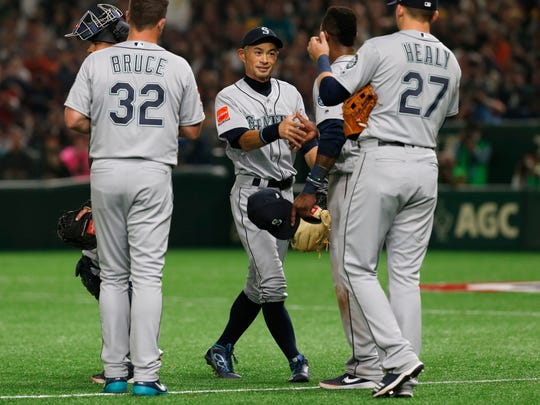 Seattle Mariners right fielder Ichiro Suzuki, center, talks to his teammates while leaving the field for defense substitution in the fourth inning of Game 1 of the Major League opening baseball series against the Oakland Athletics at Tokyo Dome in Tokyo, Wednesday, March 20, 2019. (AP Photo/Toru Takahashi)