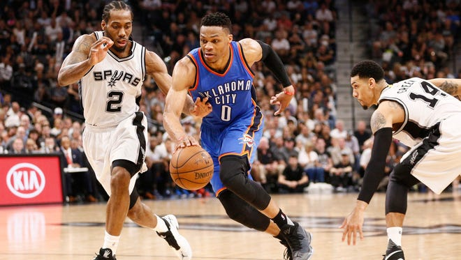 Oklahoma City Thunder point guard Russell Westbrook (0) drives for the basket between San Antonio Spurs small forward Kawhi Leonard (2) and shooting guard Danny Green (14) in game five of the second round of the NBA Playoffs.