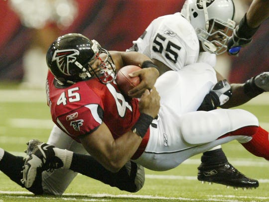 T.J. Duckett, then an Atlanta Falcons running back, is tackled by Oakland Raiders linebacker Danny Clark (55) on Sunday, Dec. 12, 2004. Duckett scored four touchdowns in the game.