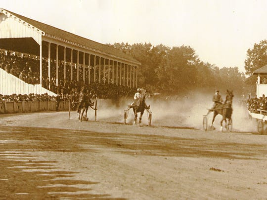 Harness racing was a popular attraction for many years at the Marion County Fair. This photo shows the grandstand and surrounding areas filled with spectators watching the action.