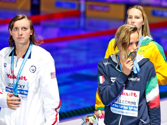 Italy's Federica Pellegrini, front right, kisses her medal as United States' silver medal winner Katie Ledecky, left, looks on after the women's 200-meter freestyle final during the swimming competitions of the World Aquatics Championships in Budapest, Hungary, Wednesday, July 26, 2017.