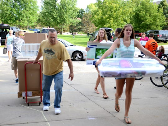 Parents, students, and volunteers are busy moving belongings into the Roy E. Downham Hall on the University of Wisconsin-Green Bay campus Thursday.