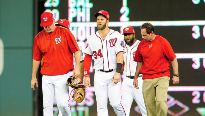 Nationals outfielder Bryce Harper walks off the field with trainer Lee Kuntz (right) after being injured in Thursday's game.
