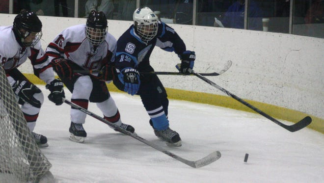 Livonia Stevenson's Sam Judd (19) races a pair of Churchill players to a loose puck during a game last week.