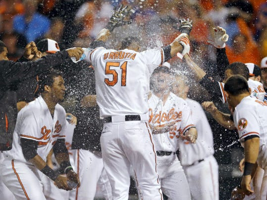Baltimore's Henry Urrutia (51) celebrates with teammates as he crosses home plate after hitting a solo home run in the ninth inning against the New York Mets on Wednesday in Baltimore. Baltimore won 5-4.