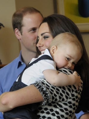 Prince George smiles in his mother Duchess Kate's arms as dad Prince William looks on during a playdate in Wellington, N.Z., on April 9 during the couple's Down Under tour.
