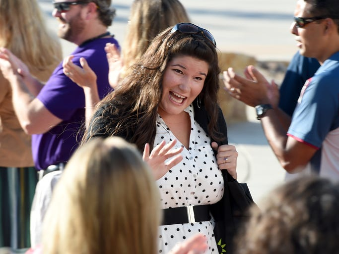 New teacher, Jessica Lynn, waves to the welcoming line as she enters the first day reception as Poudre School District staff and administrators welcomed new PSD teachers at Fossil Ridge High School Monday Aug. 11, 2014.