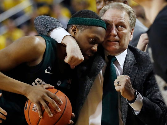 Michigan State head coach Tom Izzo holds guard Cassius Winston during the second half of an NCAA college basketball game against Michigan, Sunday, Feb. 24, 2019, in Ann Arbor, Mich. (AP Photo/Carlos Osorio)