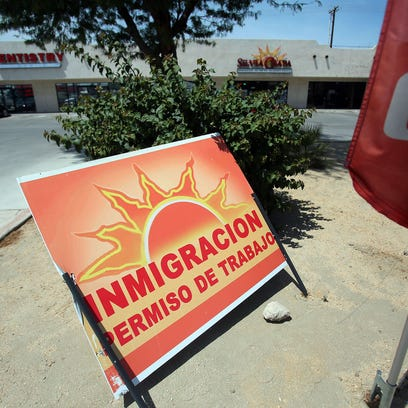 A curbside sign promotes immigration services outside