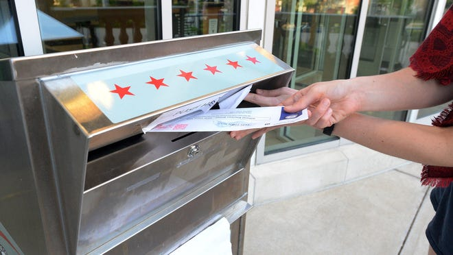 A voter drops a mail-in ballot into a box outside the Erie County Courthouse on June 2.