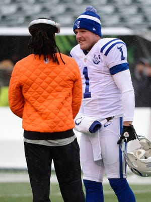 FILE -- Colts punter Pat McAfee (1) shares a laugh with Bengals cornerback Adam Jones (24) before the game at Paul Brown Stadium, Dec. 8, 2013.