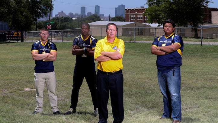 Texas Wesleyan head coach Joe Prud'homme poses for a photo with his players at the site where a new stadium will be built, as the football program is coming back after 75 years. Players pictured are Brandon Greene (left), Joe Pina (right) and Mark James (second from left).