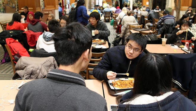 University of Iowa freshman Yanhao Wang of China chats with freshmen Yizhen Chen, left, and Yulei Zhu, both of China, as they eat lunch at the Old Capitol Town Center on Tuesday, Dec. 1, 2015.
