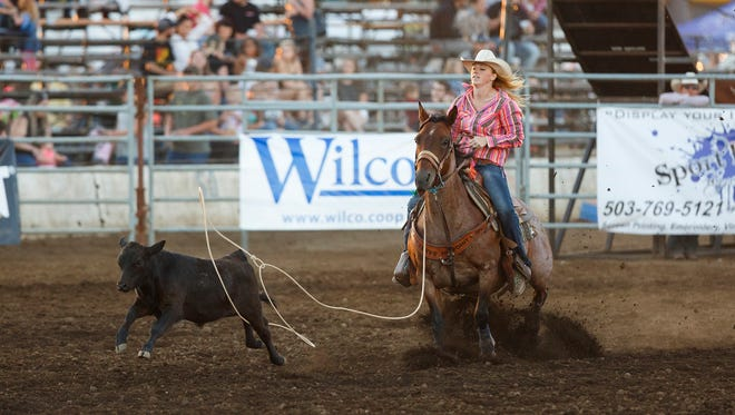 A calf slips through the lasso thrown by Katie Hoffman of Canby, Ore., during breakaway roping at the 20th annual Santiam Canyon Stampede on Friday, July 22, 2016, in Sublimity.