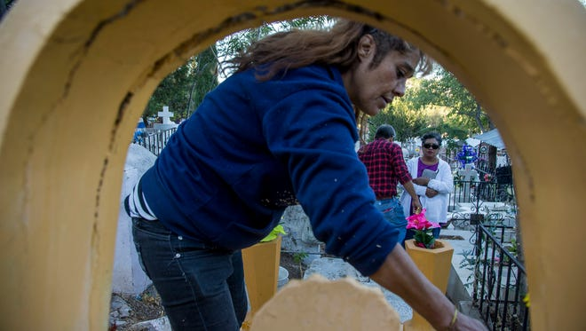 Deportee Karla Gutierrez helps families clean the graves of relatives ahead of the celebration of Dia de Los Muertos, the Day of the Dead, in Nogales, Mexico.