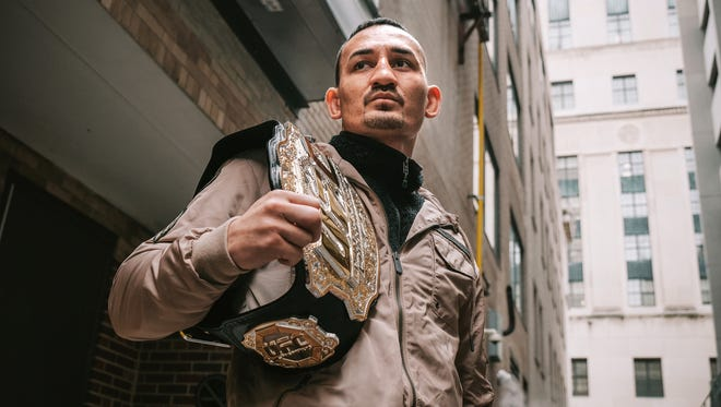 UFC featherweight champion Max Holloway poses with his belt in downtown Detroit on Thursday October 12, 2017. Holloway will face Frankie Edgar during UFC 218 at Little Caesars Arena in Detroit.