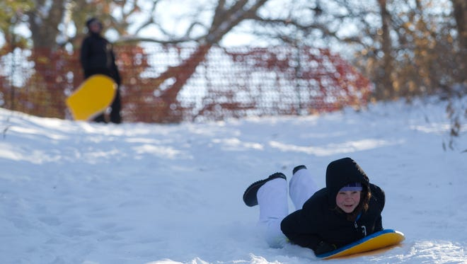 Elena Wilson, 18, sleds down a hill behind Lower City Park on Thursday, Jan. 2, 2014. Wilson and her friends, Uma Blanchard (back) and Gina Payne (not pictured) live nearby and often use the hill for sledding.  David Scrivner / Iowa City Press-Citizen