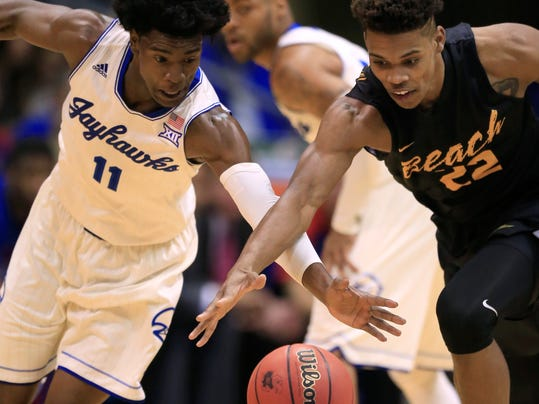 Kansas guard Josh Jackson (11) and Long Beach State forward LaRond Williams (22) chase a loose ball during the first half of an NCAA college basketball game in Lawrence, Kan., Tuesday, Nov. 29, 2016. (AP Photo/Orlin Wagner)