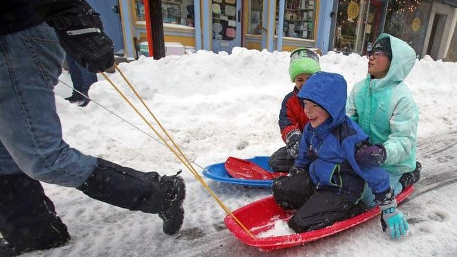 From left, Aiden Dunn, Jackson Martinez,10, and Dylan Martinez, 12 gets pulled by Christopher Dunn in the streets of Nyack during a snow storm on March 14, 2017.