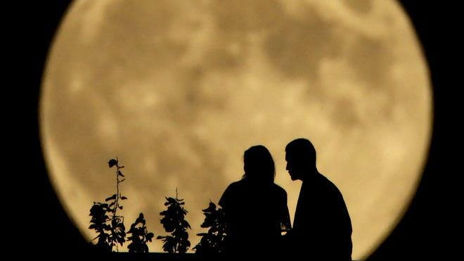 A couple sits on a bluff overlooking the Missouri River as the full Harvest Moon rises in the distance on Set. 8, 2014.