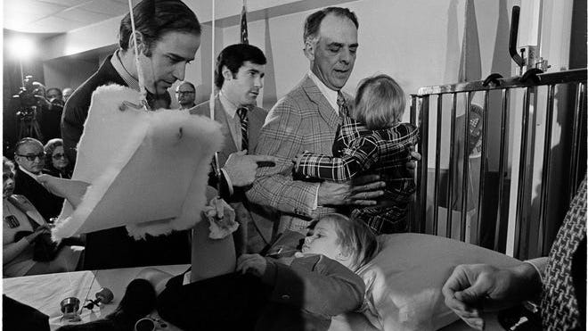 Joe Biden (left) offers words of encouragement to his bedridden son, Beau, before Bidden was sworn in as the Senator from Delaware in ceremonies in a Wilmington hospital on Jan. 5, 1973.