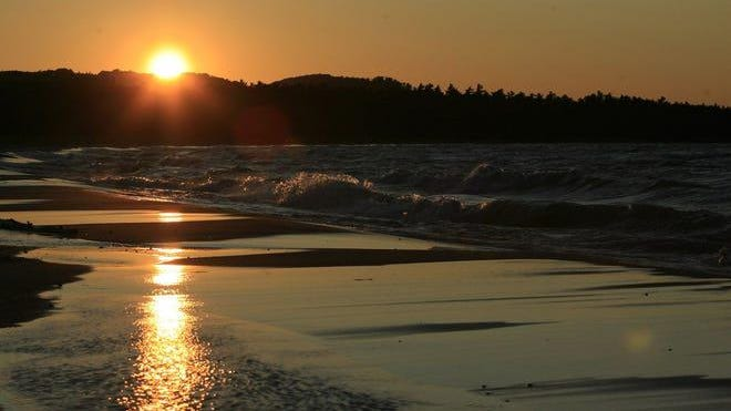 The sun sets on a beach in the Sleeping Bear Dunes National Lakeshore Park.