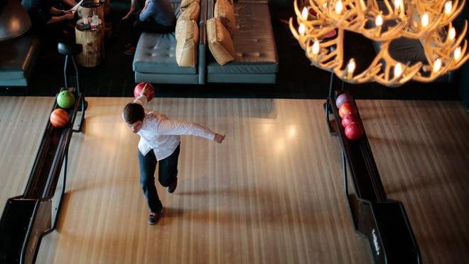 Chris Crane of Rochester makes his approach on the lanes at Punch Bowl Social, which also has ping-pong tables, arcade games, and shuffleboard.