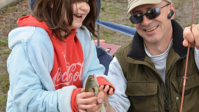 Karissa Brooks of Salem, rejoices at her first ever fish, a planted trout that she caught at a Family Fishing Event sponsored by the Oregon Department of Fish and Wildlife at St. Louis Ponds. Dad Ed Brooks, lends a helping hand.