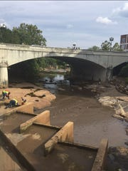 City workers try to lower a sluice gate that got stuck