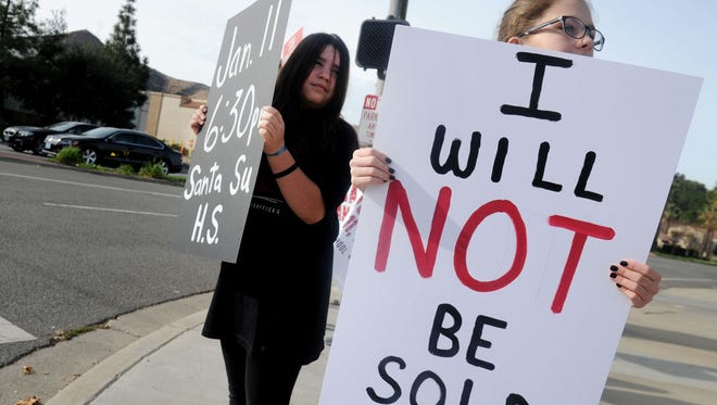 People hold signs to protest human trafficking at a demonstration in Simi Valley, California.