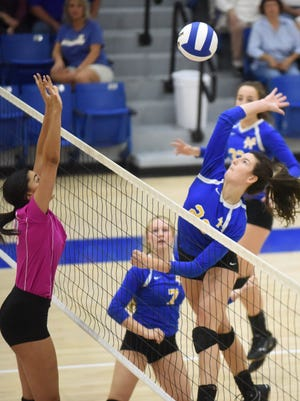 Mountain Home's Claudia Carter hammers a kill against Searcy on Thursday night at The Hangar.