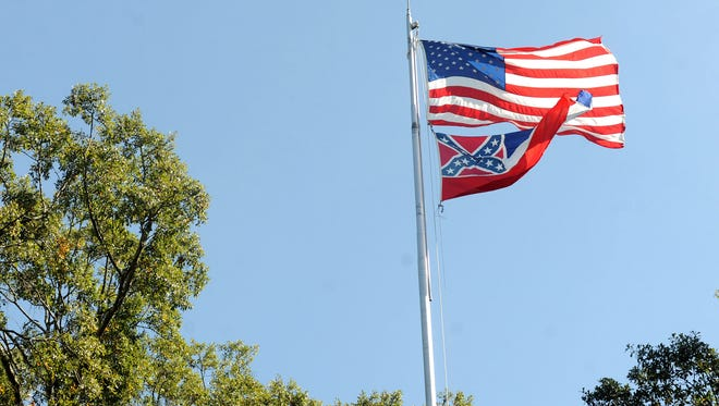 In a October 16, 2015 photo, the Mississippi state flag and U.S. flag fly in the Circle on campus at the University of Mississippi in Oxford, Miss. The state flag was removed Monday, Oct, 26, 2015, days after the student senate, the faculty senate and other groups adopted a student-led resolution calling for removal of the banner from campus.