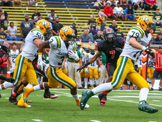 Senior Brendann Brown, escorted by linemen Theo Lucas (51) and Maverick Hansen (79), rips through the East Kentwood defense for rushing yardage.