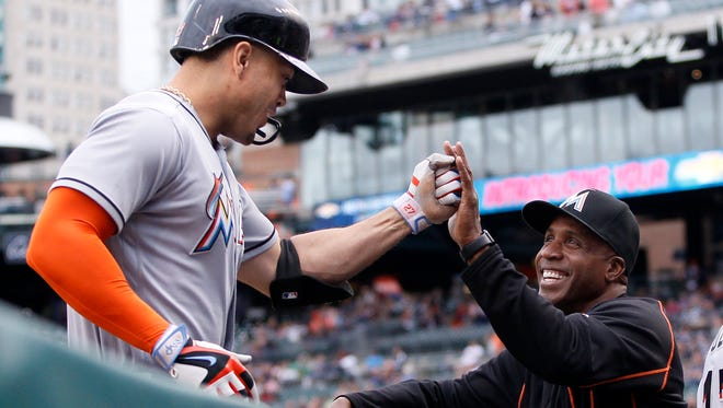 Giancarlo Stanton of the Miami Marlins is congratulated by hitting coach Barry Bonds after hitting a two-run home run against the Detroit Tigers during the second inning at Comerica Park on June 28, 2016 in Detroit, Michigan.