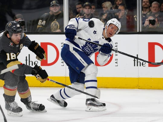 Toronto Maple Leafs center Dominic Moore, right, shoots around Vegas Golden Knights left wing James Neal during the first period of an NHL hockey game, Sunday, Dec. 31, 2017, in Las Vegas. (AP Photo/John Locher)