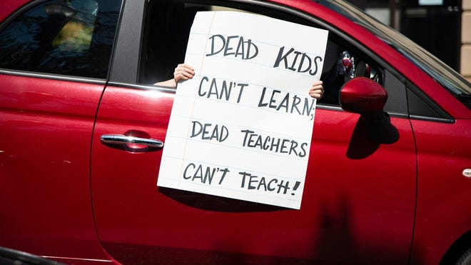 A protestor holds a sign out a car's window during the Dead Kids Can't Learn; Dead Teachers Don't Teach honkathon in front of the Andrew Johnson Building in Downtown Knoxville, Tennessee, on Friday, July 17, 2020. The honkathon was in protest of Knox County schools' reopening plan amid the coronavirus pandemic.