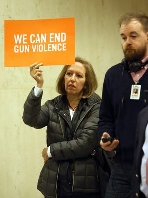 Teresa Saff holds a sign during a news conference at the Florida Capitol concerning gun bills Thursday, Jan.21, 2016, in Tallahassee.