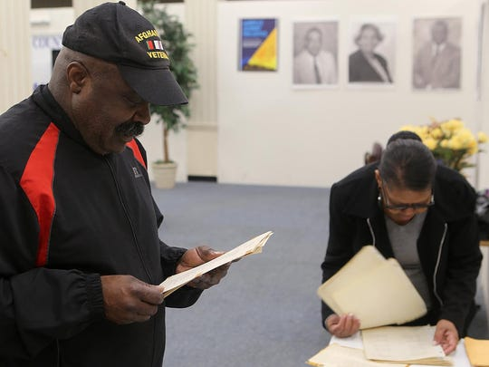 Harrell Carter, president of the Jackson chapter of the NAACP, and Wanda Drake go through Merry High School graduation records at the NAACP office downtown on Monday.