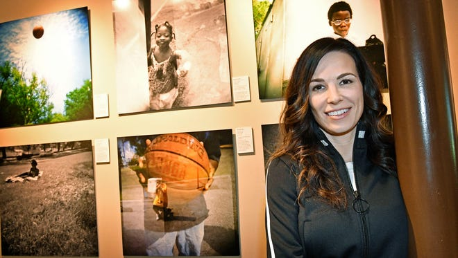 Cassidy Bentley, country star Dierks Bentley's wife, stands in front of a wall of photos that residents of Safe Haven, a Nashville shelter for homeless families, took of themselves. Friday April 7, 2017, in Nashville.