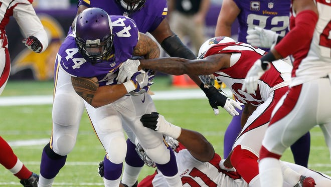 Vikings running back Matt Asiata (44) tries to break a tackle by Cardinals defensive end Ed Stinson (91) during the second half of an NFL football game Sunday, Nov. 20, 2016, in Minneapolis.