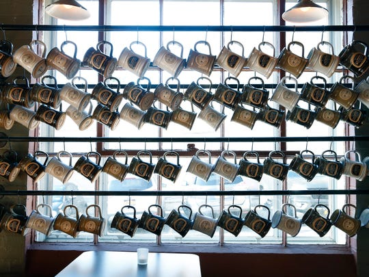 Beer mugs belonging to members of the mug club hang inside at Fairport Brewing Company. The club has 216 members and there is currently a waiting list to join.