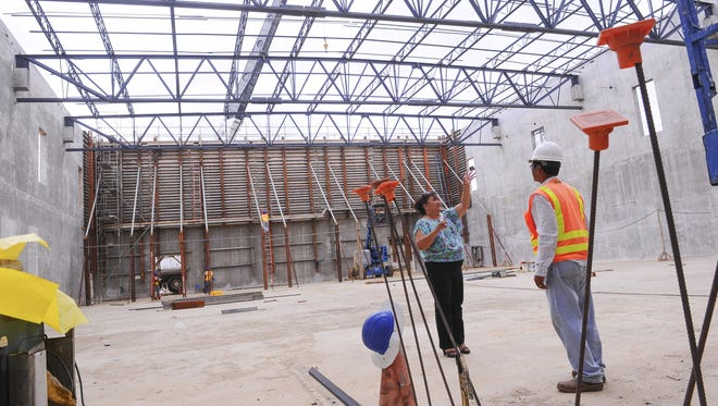Tiyan High School Principal Sophia Duenas, left, talks with Core Tech International Superintendent Andrew Cuenco on July 9 about an item she was hoping to have installed in the gymnasium, under construction.