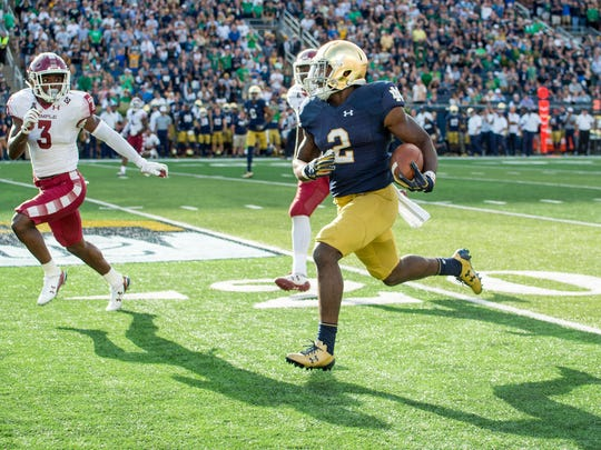 Notre Dame Fighting Irish running back Dexter Williams (2) runs the ball as Temple Owls safety Sean Chandler (3) pursues in the third quarter at Notre Dame Stadium.