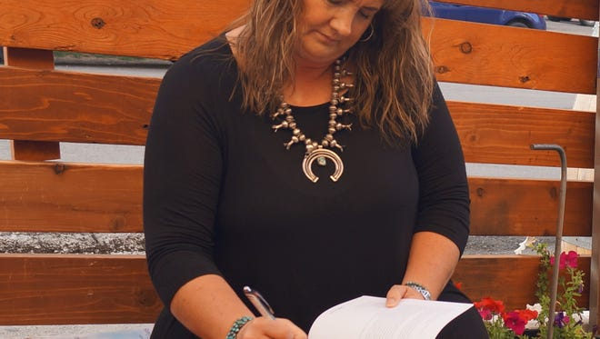 """Dana Williams signing her book, """"Conversations in the Beauty Shop"""" at her book signing party at The Hidden Tap Tuesday, Oct. 3."""