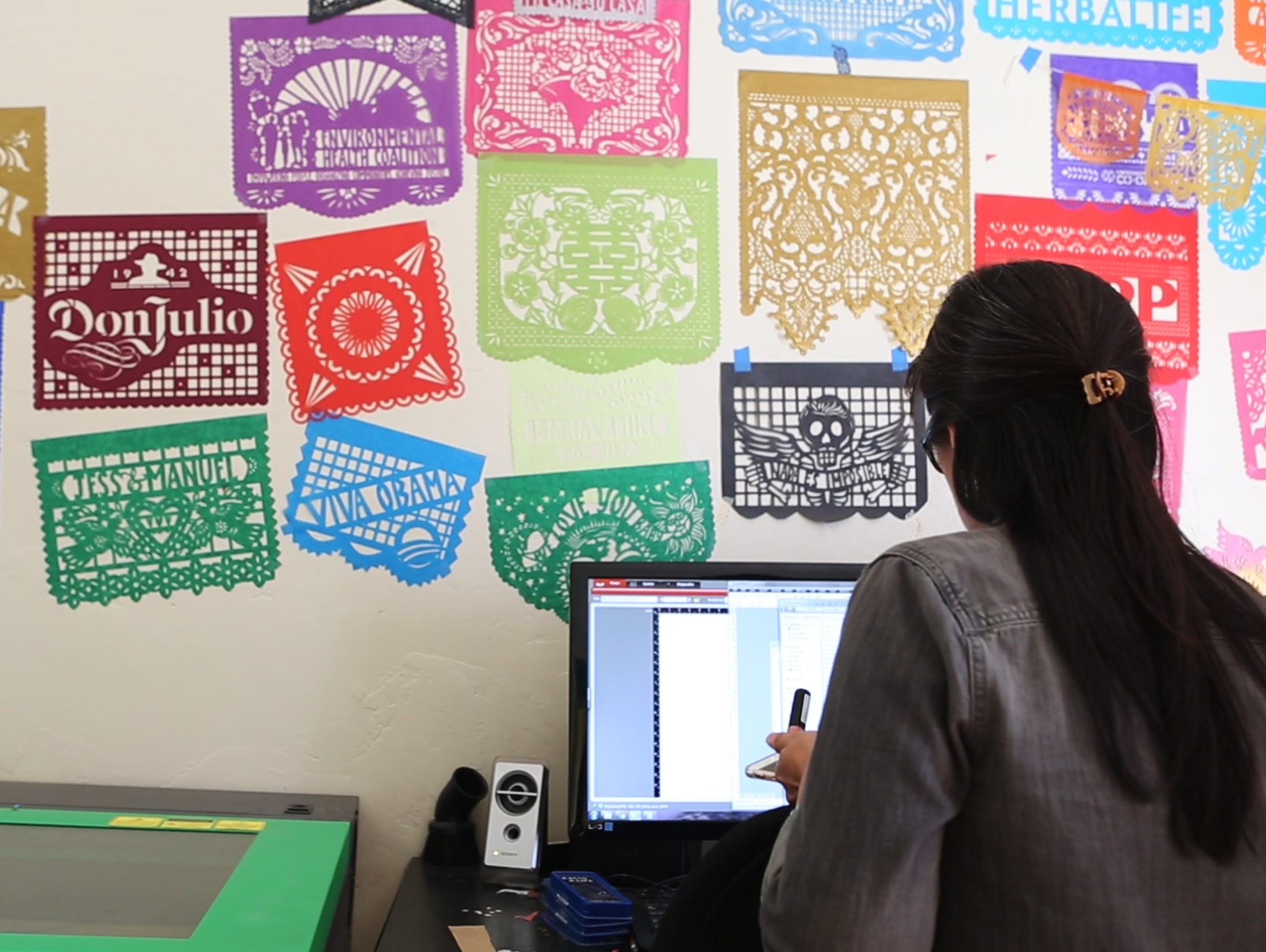 Yreina Flores looks over a design on her computer before