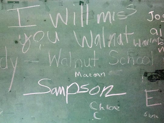Messages scrawled by students and alumni remain on the chalkboards of the vacant Walnut school building.