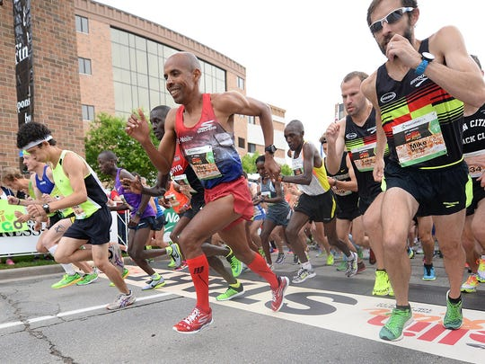 Elite runners Meb Keflezighi, center, and Mike Morgan, right, break off the starting line of the 2015 Bellin Run.